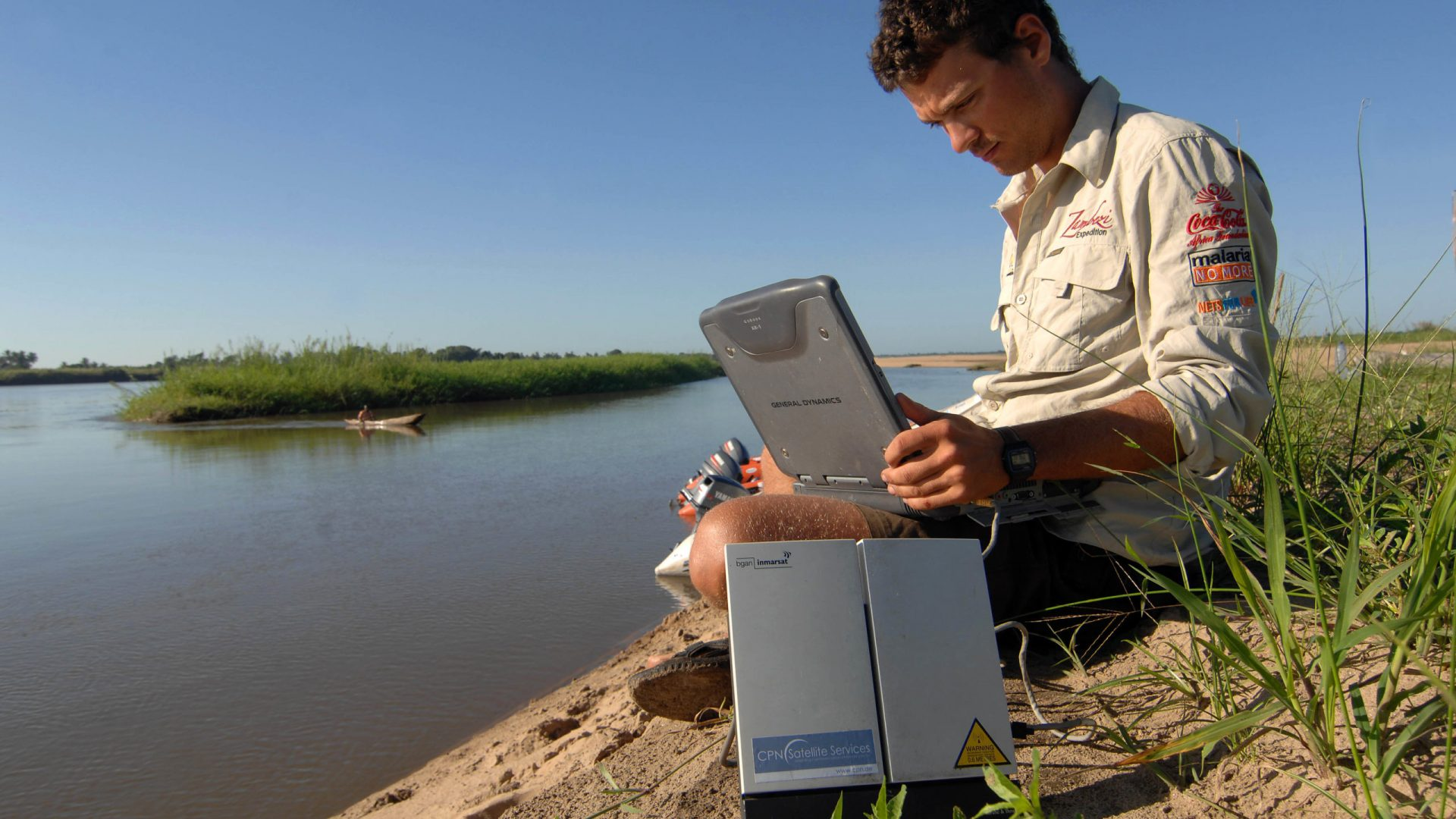 A member of the Roll Back Malaria Zambezi Expedition crew, sitting on a sandbank next to the expedition boats, uses a ruggedized notebook and a BGAN satellite terminal to check GPS points vital for navigation in the river's delta in Mozambique.
